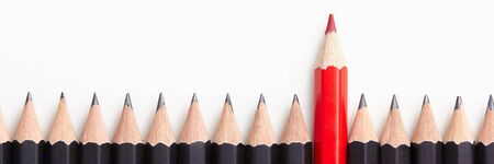 Foto de Red pencil standing out from crowd of plenty identical black fellows on white table. Leadership, uniqueness, independence, initiative, strategy, dissent, think different, business success concept - Imagen libre de derechos