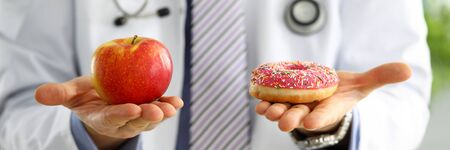 Photo for Doctor in office holding in hand pink doughnut vs red apple close-up. Products that can not be consumed in certain diseases concept - Royalty Free Image