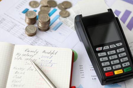 Photo for Close-up of paper and pen with family budget inscription and expenses. Detailed waste of money. Coins and terminal on desktop. Income and spending concept - Royalty Free Image