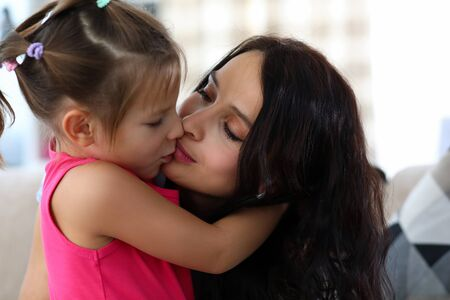Foto de Portrait of lovely mom and happy child enjoying spending funny time together. Warm relationship between daughter and mommy. Childhood and parenthood concept - Imagen libre de derechos