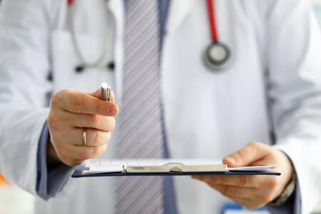 Photo pour Hand of male GP passing to patient silver pen asking to sign some paper documents close-up - image libre de droit