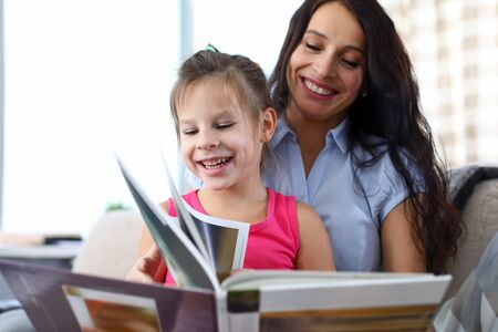 Foto de Portrait of beautiful mother teaching declaiming happy daughter. Lovely woman and little girl looking at magazine with happiness. Childhood and motherhood concept - Imagen libre de derechos
