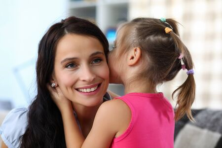 Photo pour Portrait of smiling woman enjoying spending funny time with daughter. Little girl whispering secret in ear of happy mother. Childhood and family concept - image libre de droit