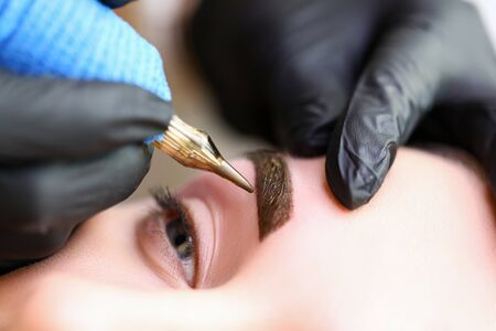 Photo pour Beauty masters hands do permanent eyebrow makeup. Minimal trauma to skin. Eyebrow microblading is performed using manipulator handle and special nozzle with needles. Cosmetologist skill level - image libre de droit