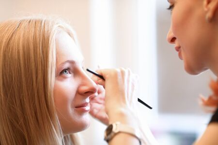 Photo pour Beautician draws model eyebrows on face model. Powder technology creates effect tinted eyebrows. Various transitions in shading. Girl follows trends special fashion cosmetology procedure - image libre de droit