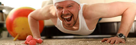 Close-up of man exercising and pushing up. Sportive male in apartment on quarantine training to lose weight. Bodyweight control at home, athletic character in house