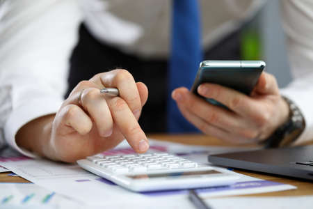 Photo for Close-up of hands of businessman using smartphone and calculator to count financial details. Man at workplace with phone, documents and pen. Banking and economy - Royalty Free Image