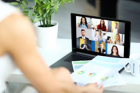 Photo pour Woman talking with international colleagues using online video chat service at workplace closeup - image libre de droit