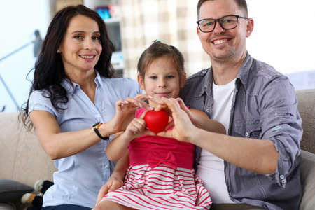 Photo for Portrait of cheerful lovely parents and little kid holding red heart together. Cheerful daughter sitting on father knees and smiling sincerely. Happy family concept - Royalty Free Image