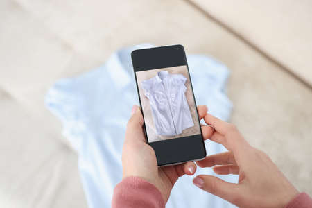 Photo pour Female hand holds smartphone and makes photos of blue shirt. Sale of used things concept - image libre de droit