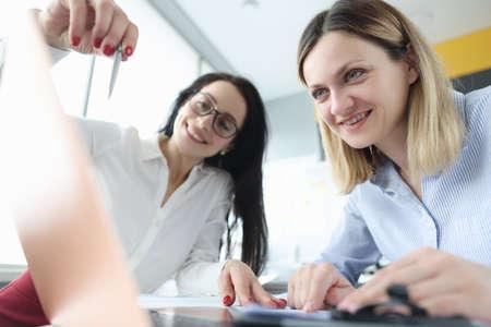 Foto de Two businesswoman are discussing business processes by demonstrating them on laptop - Imagen libre de derechos
