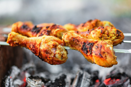 Chicken legs being roasted over charcoal