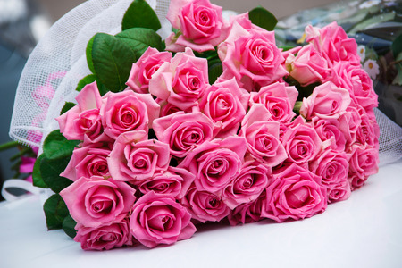 Grouping bouquet of beautiful pink roses on a car hood