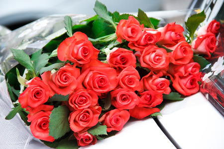 Grouping bouquet of beautiful red roses on a car hood