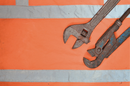 Adjustable and pipe wrenches against the background of an orange signal worker shirt. Still life associated with repair, railway or plumbing works