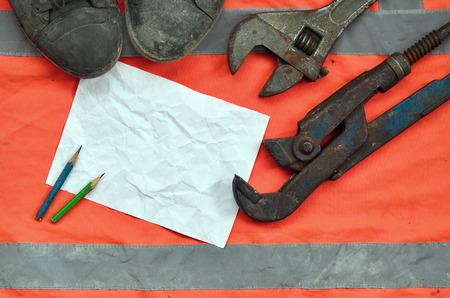 Adjustable wrenches with old boots and a sheet of paper with two pencils. Still life associated with repair, railway or plumbing works