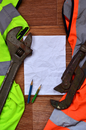 A crumpled sheet of paper with two pencils surrounded by green and orange working uniforms and adjustable wrenches. Still life associated with repair, railway or plumbing works