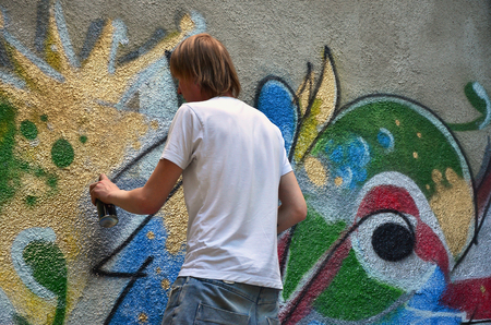 Photo in the process of drawing a graffiti pattern on an old concrete wall. Young long-haired blond guy draws an abstract drawing of different colors. Street art and vandalism concept