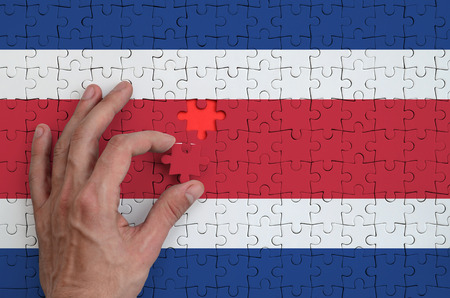 Costa Rica flag  is depicted on a puzzle, which the man's hand completes to fold.