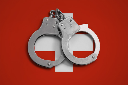 Switzerland flag  and police handcuffs. The concept of observance of the law in the country and protection from crime.