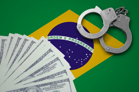 Brazil flag  with handcuffs and a bundle of dollars. The concept of illegal banking operations in US currency.