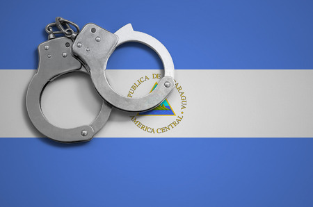 Nicaragua flag  and police handcuffs. The concept of crime and offenses in the country.