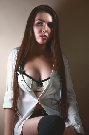 Photo for Young and sexy intern medical institution in a white shirt and white underwear with a stethoscope around his neck sitting in a room with beige walls. Attractive caucasian nurse girl with a stethoscope - Royalty Free Image