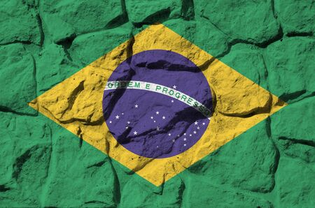Brazil flag depicted in paint colors on old stone wall close up. Textured banner on rock wall background