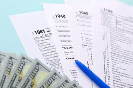 Photo pour Tax forms lies near hundred dollar bills and blue pen on a light blue background. Income tax return. - image libre de droit