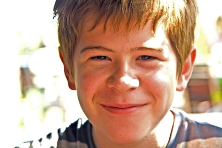 young boy with red hair is smiling and happy