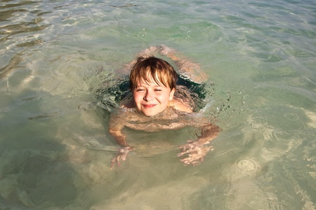 boy has fun in the wonderful warm ocean and enjoys the water
