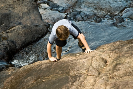 young boy climbing up a rock