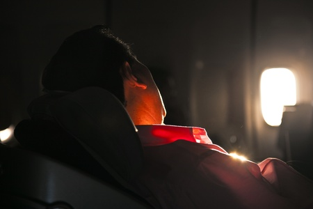 Photo pour man sleeping in the seat of an aircraft in sunrise - image libre de droit