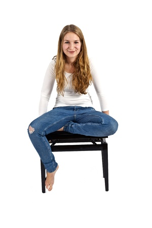 Full length portrait of happy beautiful girl sitting on a piano chair, isolated on white background