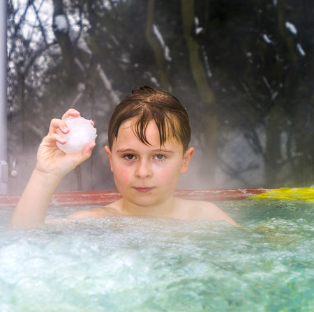 boy enjoys swimming in the warm outdoor pool with a snowball in his hand