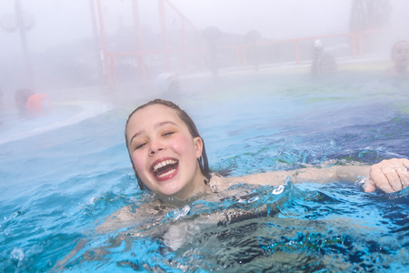 young girl swims in the outside area of a thermal pool in wintertime and in fog