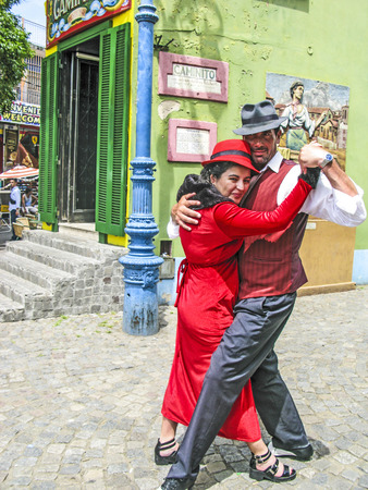 BUENOS AIRES, ARGENTINA - JAN 26, 2015: tango dancer pose for tourists in Caminito Street, Buenos Aires, Argentina. Caminito is a traditional alley, located in La Boca.