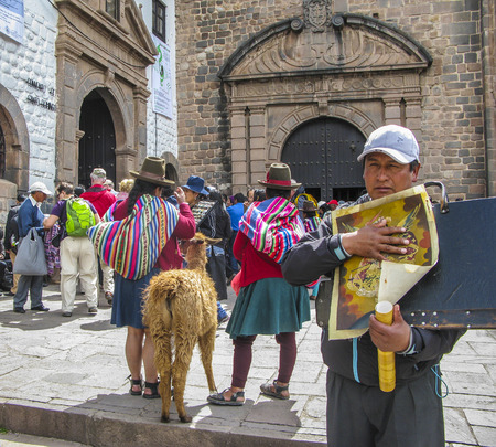 CUSZO, PERU - JAN 16, 2015: indian woman pose with a lama for tourists in Cuzco, Peru to earn some money. An indio man sells paintings.