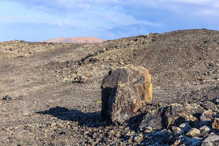 Volcanic bomb in front of volcano Montana Colorada in Lanzarote, Canary Islands, Spain