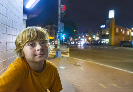 cute boy smiles tired while sitting outside by night next to the street