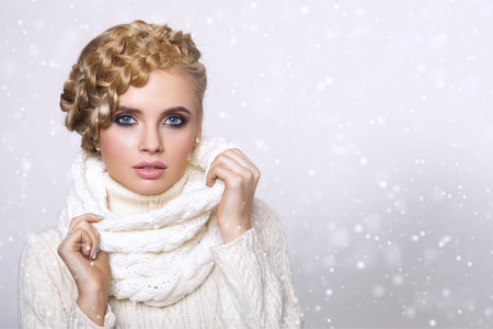 Foto de portrait of a beautiful young blonde woman on a light background. hair tied in a braid. girl wearing a warm sweater and scarf. copy space. - Imagen libre de derechos
