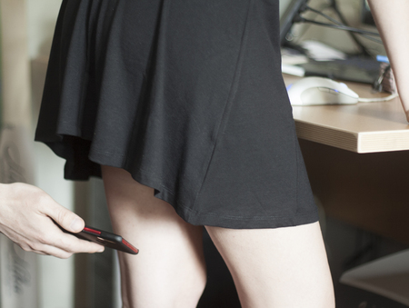 Photo pour A man photographs a mobile phone under the skirt of a woman. Sexual harassment at work - image libre de droit