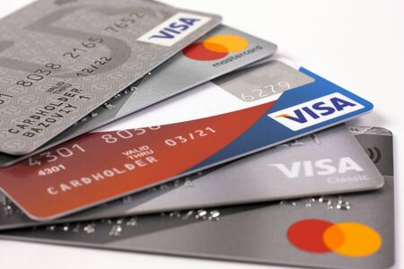 Photo pour February 11, 2020. Novosibirsk, Russia. Several bank credit cards with Visa and Mastercard logos on a white background - image libre de droit