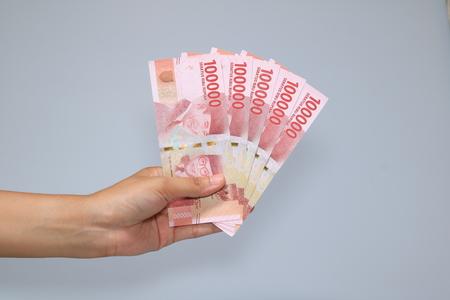 Photo pour woman hand showing rupiah Indonesian money - image libre de droit