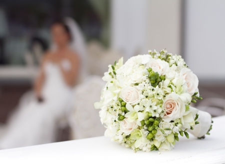 Photo pour Beautiful white wedding bouquet with bride sitting in the background - shallow dof  - image libre de droit