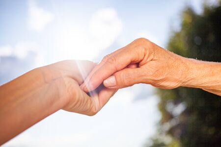 Photo for close-up of tender gesture between two generations. Young woman holding hands with a senior lady. Blue sky background - Royalty Free Image