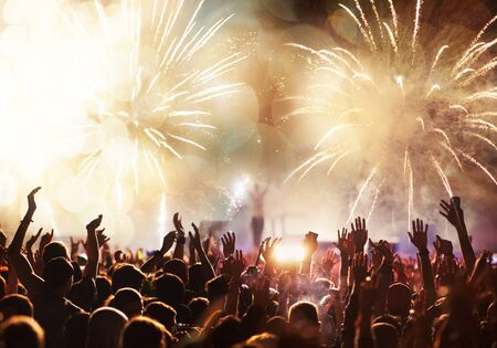 Photo pour crowd with raised hands and fireworks new year banner - image libre de droit