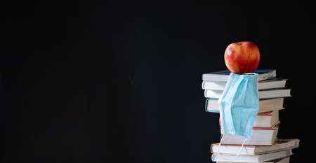 Photo for back to school during covid pandemic pile of books and medical mask - Royalty Free Image