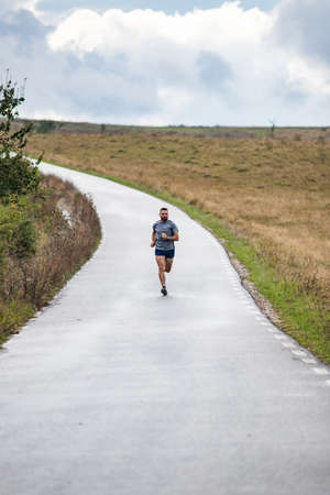 Photo for young man running on country road - Royalty Free Image