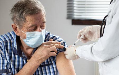 Photo pour elderly man getting coronavirus vaccine - image libre de droit
